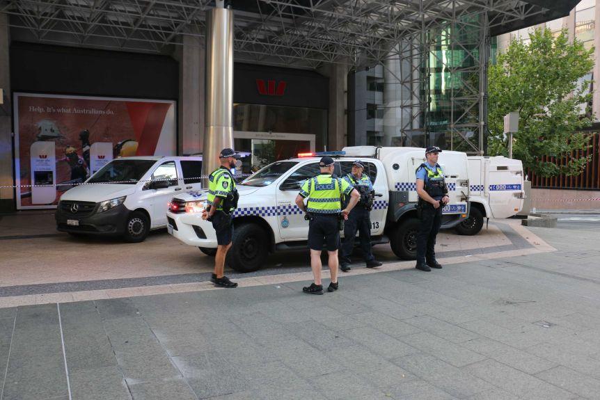 La police se tient devant les véhicules de police devant la banque Westpac.  La bande de police est en place.