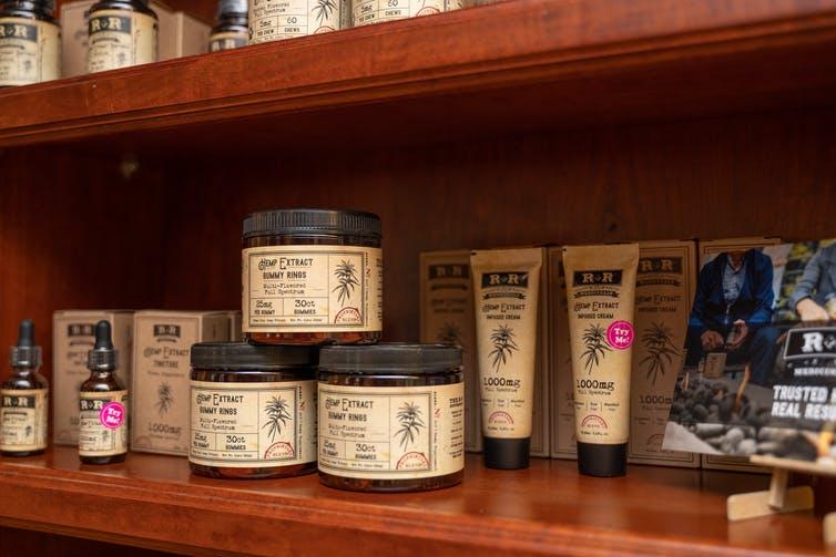 Étagère en bois avec divers produits CBD de l'étiquette R + R Medicinals dessus