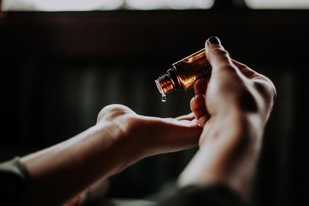 personne tenant une bouteille en verre ambré