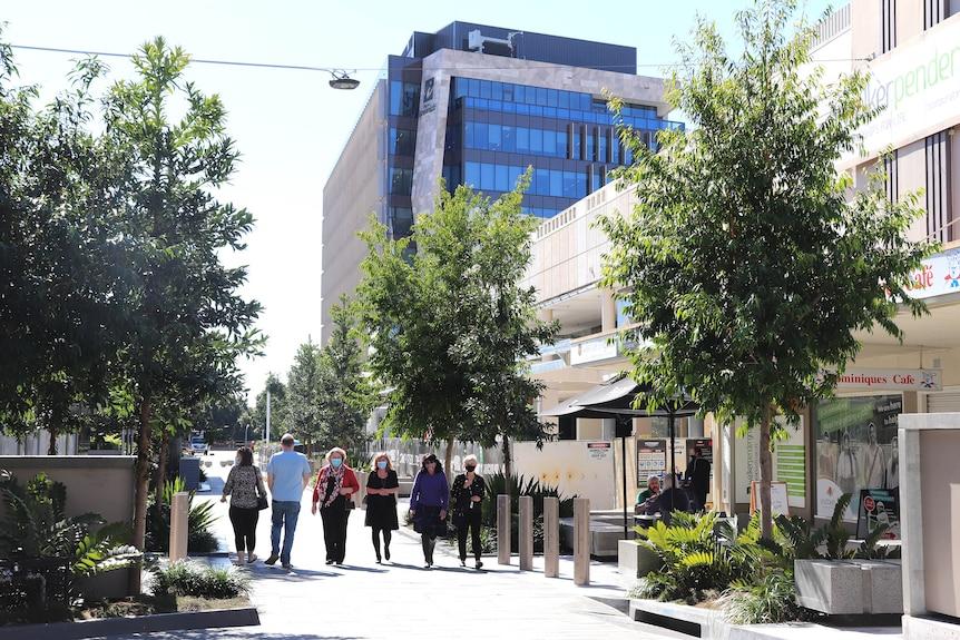 Cinq personnes marchant dans le centre commercial d'Ipswich