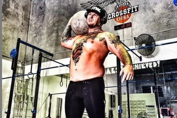 Un homme se tient dans une salle de sport tenant un ballon.