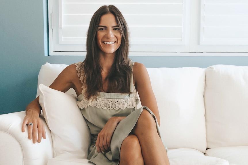 Une femme est assise sur un salon blanc