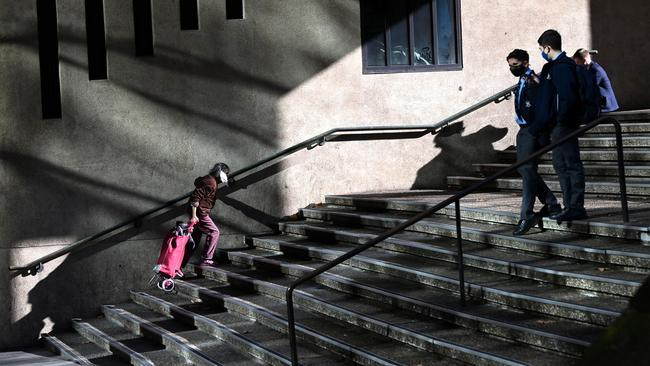 Des élèves de l'école et un marcheur solitaire étaient les seules personnes vues sur les marches de la gare de l'hôtel de ville vers le QVB.  Photo : Jeremy Piper / NCA NewsWire