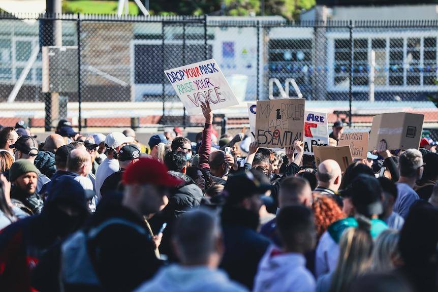 une grande foule de personnes tenant des pancartes