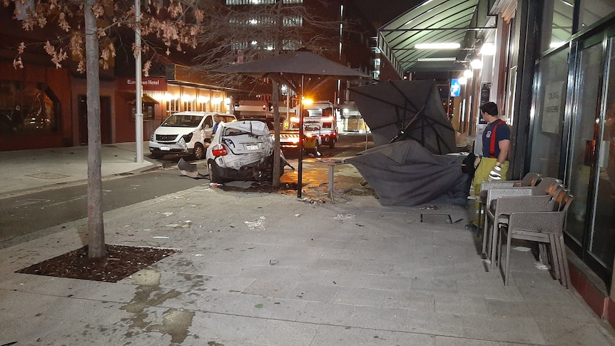 Un homme en uniforme de secouriste regarde une voiture brisée devant un restaurant.