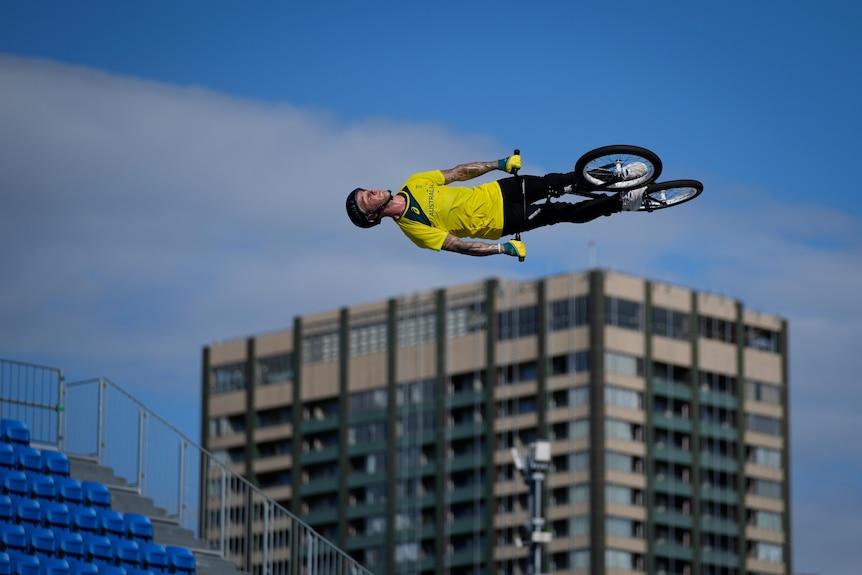 Un coureur sur un vélo BMX est haut dans le ciel et sur le côté, avec un immeuble en arrière-plan.